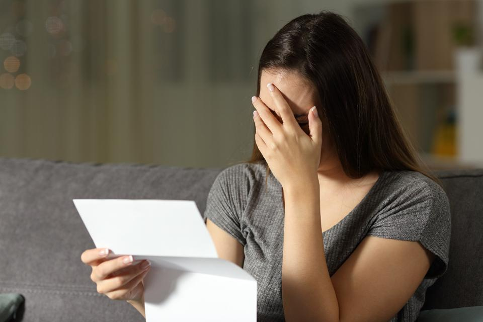 Sad woman reading a letter in the dark
