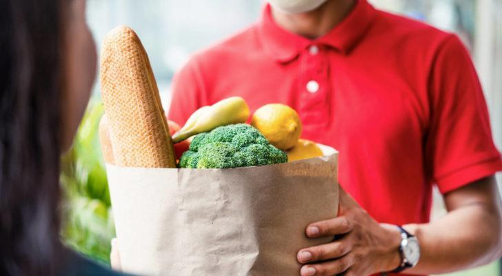a delivery man in a red shirt dropping off a bag of groceries to represent food and beverage stocks